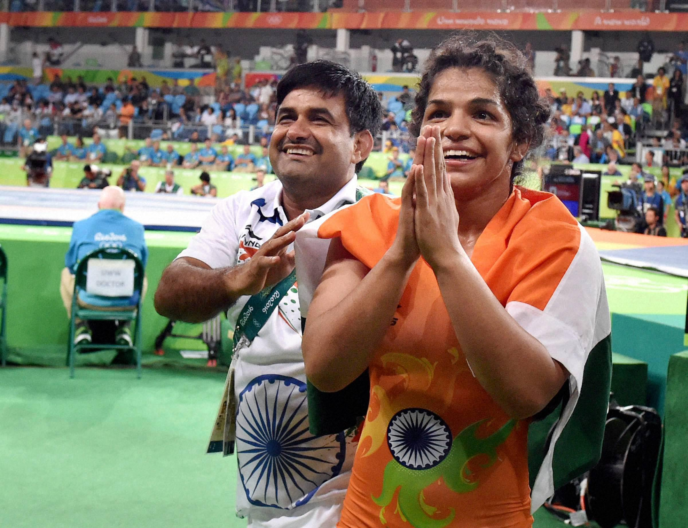 Rio de Janerio : India's Sakshi Malik along with her coach Kuldeep Singh celebrates after winning bronze medal of the women's wrestling freestyle 58-kg competition, at the 2016 Summer Olympics in Rio de Janerio, Brazil on Wednesday. PTI Photo by Atul Yadav (PTI8_18_2016_000217B)