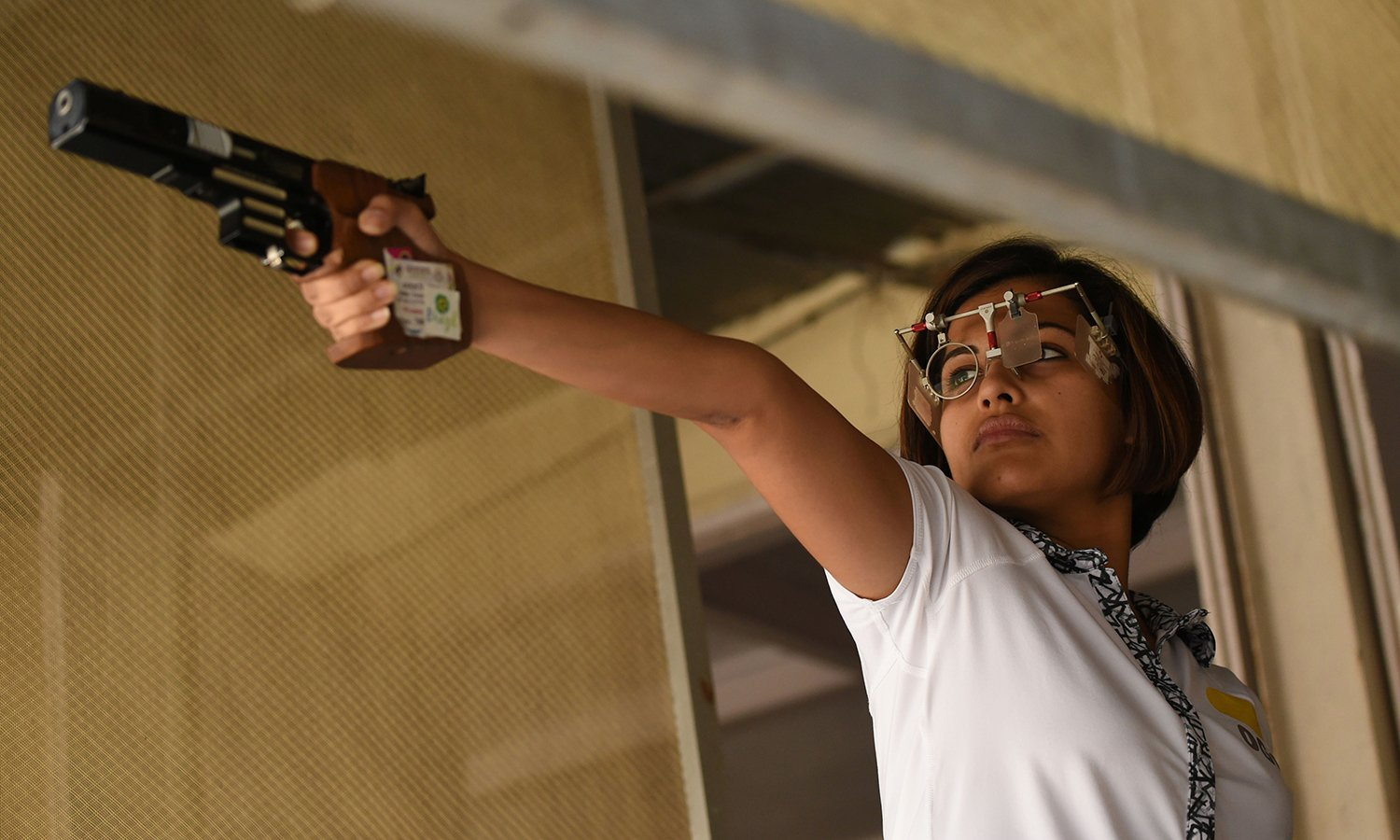 TO GO WITH 'OLY-2016-IND-shooting', INTERVIEW by Peter HUTCHISON In this photograph taken on April 25, 2016, Indian shooter Heena Sidhu lines up a shot as she takes part in a training session at the Maharshtra Rifle Association firing range in Mumbai. With one hand in her pocket and the other on the trigger, India's ace shooter Heena Sidhu is trying to keep it cool as she targets glory at the Rio Olympics. The 26-year-old, who is a qualified dentist, may be desperate to put a smile on the face of medal-starved fans back home but she knows that she must stay relaxed despite carrying the huge burden of an expectant nation. / AFP PHOTO / INDRANIL MUKHERJEE / TO GO WITH 'OLY-2016-IND-shooting', INTERVIEW by Peter HUTCHISON